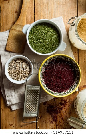 Middle Eastern cuisine: bowl of sumac, dried parsley, sunflower seeds, ginger in powder. Sumac powder is used in Arabic cuisine to add zest and flavour to dishes. - stock photo