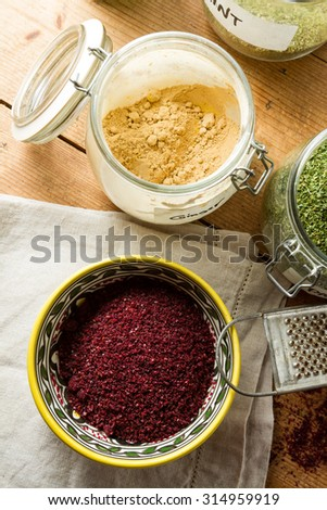 Middle Eastern cuisine: bowl of sumac, jar with dried ginger, mint and other herbs. Sumac powder is used in Arabic cuisine to add zest and flavour to dishes. - stock photo
