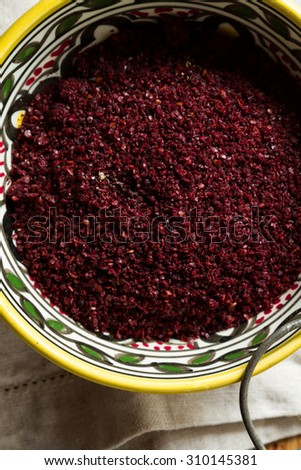 Middle Eastern cuisine: close-up on bowl of sumac. Sumac powder is used in Arabic cuisine to add zest and flavour to dishes. - stock photo