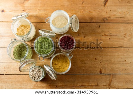 Middle Eastern cuisine: jars of spices and dried herbs ready to be used. Powdered ginger and garllic, cumin, dried parsley and mint, sumac and sunflower seeds. Copy space. - stock photo