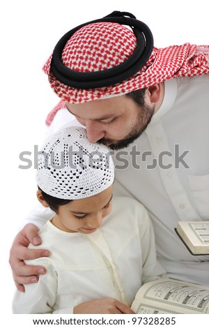 Middle eastern education, father kissing son while reading Koran - stock photo