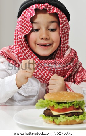 Middle Eastern little boy with hamburger - stock photo