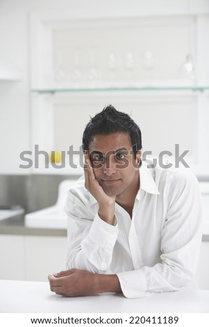 Middle Eastern man leaning on counter in kitchen - stock photo
