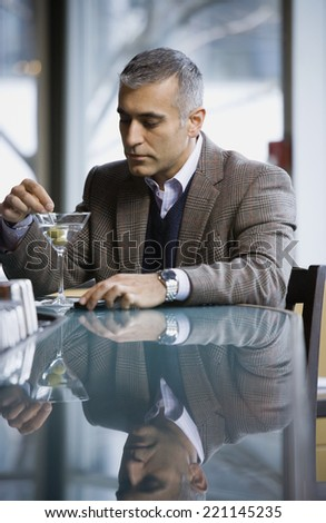 Middle Eastern man stirring cocktail - stock photo