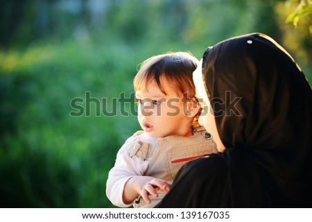 Middle Eastern Muslim mother playing with her little baby in green park and holding him in arms - stock photo