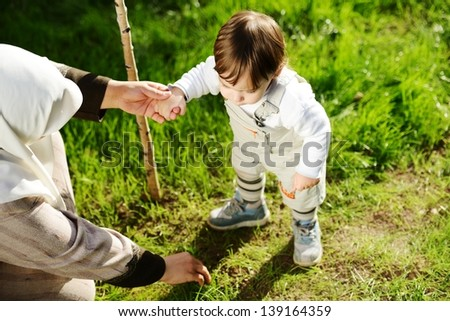 Middle Eastern Muslim mother playing with her little baby in the garden planting the new tree - stock photo