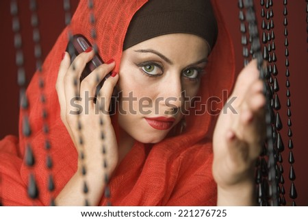 Middle Eastern woman talking on cell phone - stock photo
