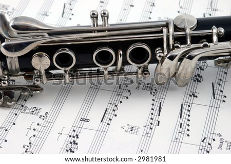 Middle of a clarinet with holes and keys lying on some sheet music