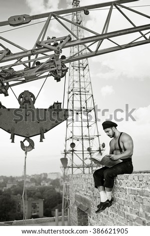 Middle of a workday. Monochrome shot of a retro construction worker relaxing with a newspaper on top of a brick wall - stock photo