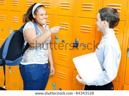 Middle school boy and girl laughing and joking together by their lockers. - stock photo