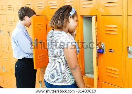 Middle school girl and boy at their lockers between classes. - stock photo