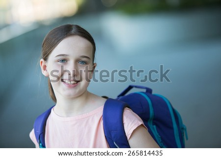 middle school girl in a pink shirt with a purple backpack - stock photo