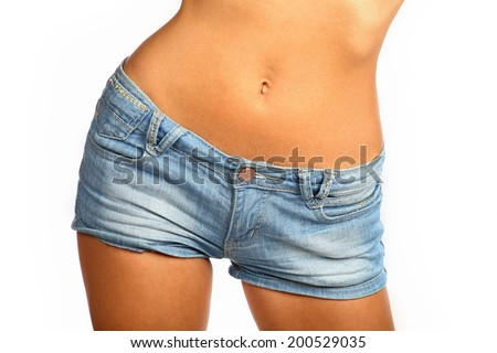 Middle section of a young and fit woman with short denim pants. Woman in jeans texas shorts - stock photo