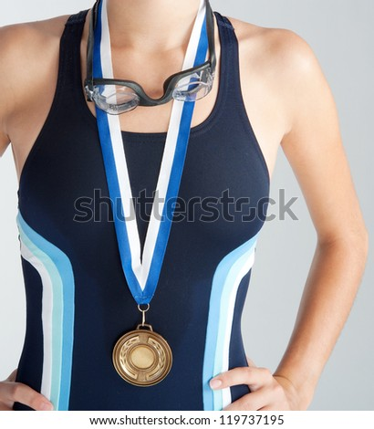 Middle section of an olympic swimmer's body wearing a gold medal and a blue sports swimming costume against a white background. - stock photo