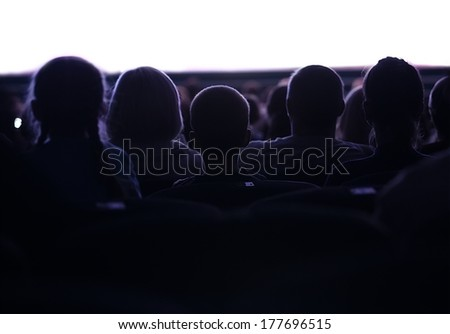 Middle shot of sihouettes of people from back watching cinema or performance with white empty space - stock photo