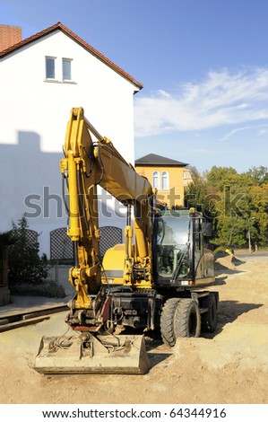 middle size yellow excavator on the construction site in the historical part of Jena, Thuringia, Germany