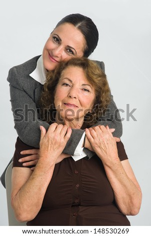 Middleaged woman is cuddling on her mother while she sits - stock photo