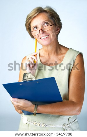 Middleaged woman with clipboard looking up for inspiration - stock photo