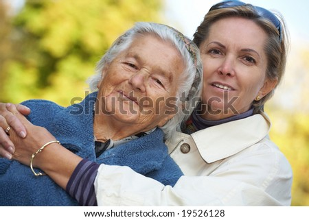 Middleaged woman with her elderly mother. Focus on the daughter. - stock photo