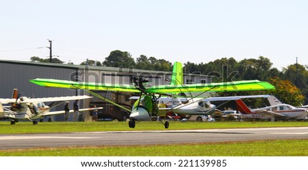 MIDDLESEX, VA - SEPTEMBER 27, 2014: A lime green ultralight  airplane high above Hummel field airport in the wings wheels and keels annual show at the  Hummel airfield airstrip in Middlesex VA