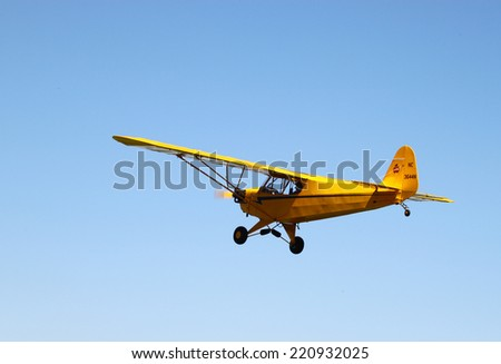 MIDDLESEX, VA - SEPTEMBER 27, 2014: A yellow piper cub high above Hummel  field airport in the wings wheels and keels annual show at the Hummel airfield airstrip in Middlesex VA