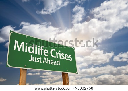 Midlife Crises Just Ahead Green Road Sign with Dramatic Clouds, Sun Rays and Sky. - stock photo