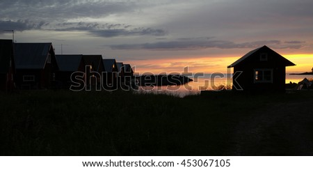 Midnight light and fisherman cabins on the Swedish east coast after the sunset - stock photo