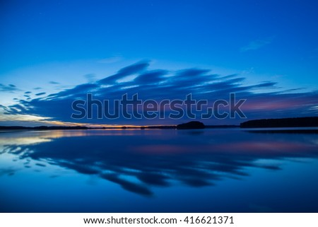 Midnight light over calm lake  - stock photo