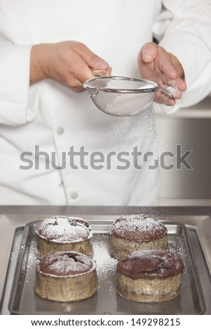 Midsection closeup of male chef icing sugar over chocolate cakes at counter in commercial kitchen - stock photo