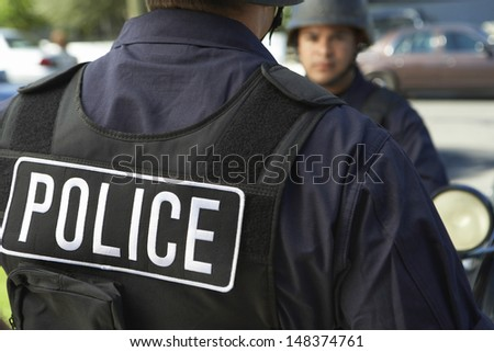 Midsection closeup of policeman wearing protective vest outdoors