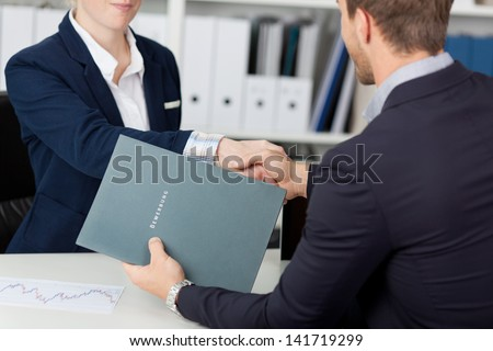 Midsection of a businessman shaking hands with a female interviewer in office - stock photo