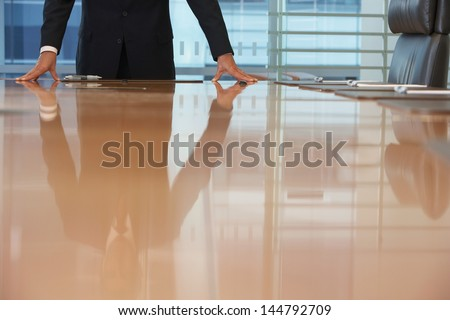Midsection of a businessman standing with hands on conference table - stock photo