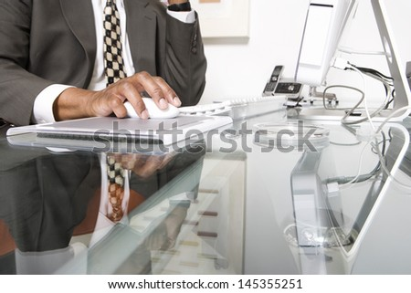 Midsection of a businessman using computer at office - stock photo