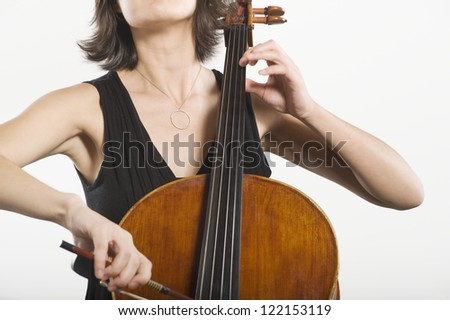 Midsection of a female playing cello classical music instrument isolated over white background