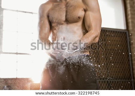 Midsection of a muscular man applying chalk powder at the gym - stock photo