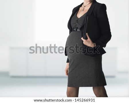 Midsection of a pregnant businesswoman walking with folder against blurred background - stock photo