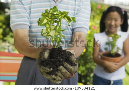 Midsection of a senior man holding a plant with grandchild standing in background - stock photo