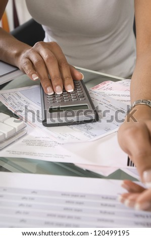 Midsection of a woman calculating budget at home - stock photo