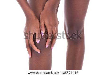 Midsection of African American woman suffering from knee pain against white background - stock photo