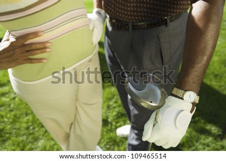 Midsection of an African American couple standing with golf club