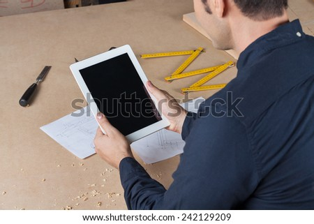 Midsection of architect holding digital tablet at table in workshop - stock photo