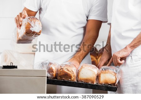 Midsection Of Baker's With Packed Bread Loaves In Bakery - stock photo