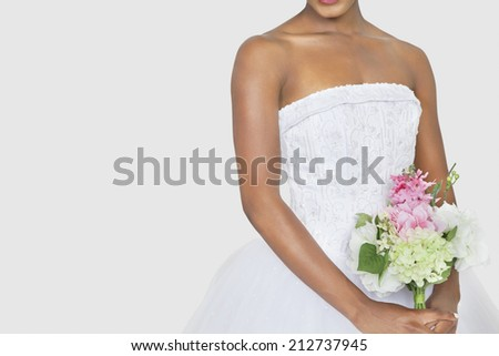 Midsection of bride holding bouquet over gray background - stock photo