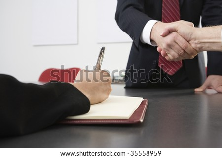 Midsection of business men shaking hands at an office. - stock photo
