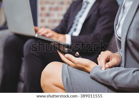 Midsection of business people using mobile phone and laptop on sofa in office
