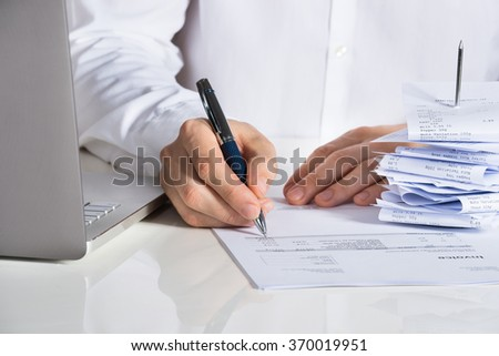 Midsection of businessman analyzing invoice by laptop at office desk - stock photo