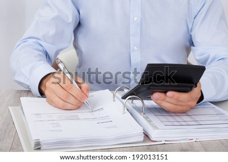 Midsection of businessman calculating financial expenses at desk - stock photo
