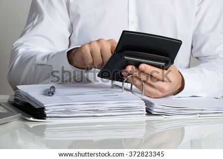 Midsection of businessman calculating invoice at office desk - stock photo