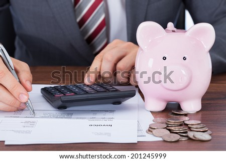 Midsection of businessman calculating invoice by piggybank and coins on desk - stock photo