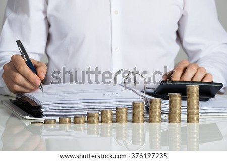 Midsection of businessman calculating invoice with stacked coins arranged at office desk - stock photo
